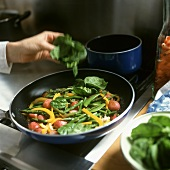 Adding spinach to vegetables in a frying pan