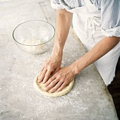 Flattening pizza base by hand