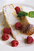 Two pieces of sponge cake with raspberries and mint