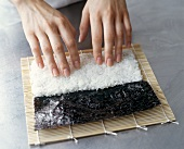 Making Maki Sushi: Hands Pressing Rice onto a Sheet of Nori