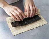 Maki-Sushi zubereiten: Noriblatt mit Bambusmatte aufrollen
