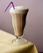 Chocolate milk in glass with lilac straw