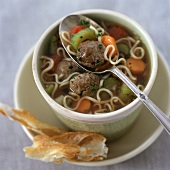 A Cup of Meatball Soup with Noodles and Vegetables