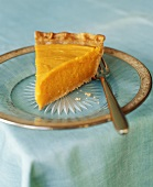 A slice of pumpkin pie with fork