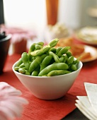 Green soya beans in their pods in white bowl