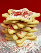 Star biscuits with icing and red sprinkles, in a pile