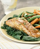 Salmon fillet on spinach with sugar snap peas and carrots