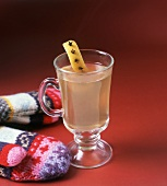 Hot Toddy Served in a Glass Mug with Lemon Rind with Cloves Garnish; Mittens