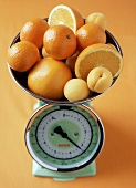Citrus fruits and apricots on scales