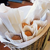 Fresh Baked Bread in Paper Bags in a Large Basket