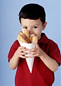Small boy holding paper bag of strips of pizza