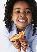 Girl holding toast with a bite taken
