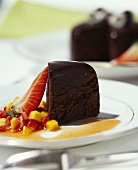 A piece of chocolate cake with fruit sauce
