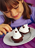 Girl decorating soft ice cream in chocolate shell