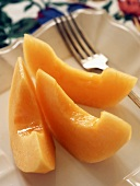 Three slices of sweet melon on plate