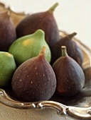 Green and purple figs in silver bowl