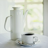 Cup of black coffee in front of coffee pot