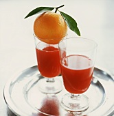 Two glasses of blood orange juice on tray