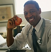 Laughing doctor holding fresh Gala apple