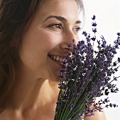 Smiling woman smelling lavender flowers