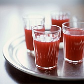 Four glasses of blood orange juice on tray