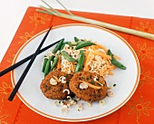 Sambal Salmon Cakes with Asian Noodles, Carrots and Pea Pods on a Plate with Chopsticks