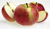 Three red apples, one cut open