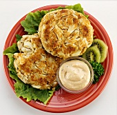 Two crab cakes with spicy sauce on red plate