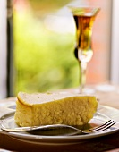 Piece of cheesecake on plate with fork; glass of dessert wine