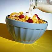 Pouring milk over cornflakes with raspberries