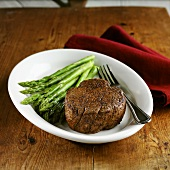Beef fillet with green asparagus on wooden table