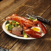 Lobster and beef fillet with vegetables on platter