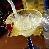 Cocktail spritzend in Martiniglas eingiessen