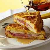 Pouring maple syrup over French toast with ham
