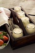 Yoghurt in jars in wooden crate; strawberries in bowl