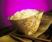 Cooked sticky rice in bowl, chopsticks beside it