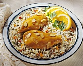 Orange-glazed chicken breasts with almonds on bed of rice