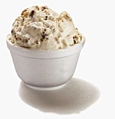 Vanilla ice cream with caramel and nuts in a Styrofoam bowl