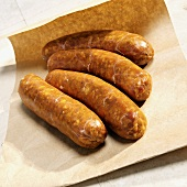 Four Italian sausages on brown paper