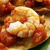 Shrimps and tomato salsa on tortilla chips (close-up)