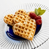 Heart-shaped waffles with raspberries and fresh mint
