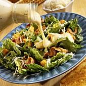 Cäsarsalat mit Dressing begiessen