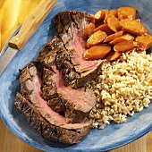 Slices of beef steak with carrots and rice