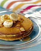 Pancakes with Banana Slices, Syrup and Peanuts
