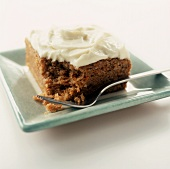 A Square Piece of Carrot Cake with Cream Cheese Frosting on a Square Green Plate with a Fork