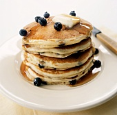 A Stack of Blueberry Pancakes with Melting Butter and Syrup
