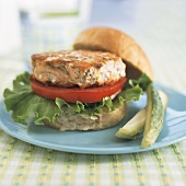 A Fried Salmon Cake on a Roll with Tomato and Lettuce