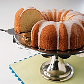 Lifting a Slice of Bundt Cake from a Whole Iced Bundt Cake