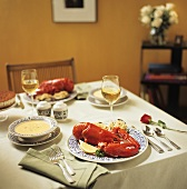 A Table Setting with Steamed Lobster, Clams Casino, Soup, Dessert and White Wine