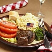 A Steak Fillet with an American Flag Toothpick, Mashed Potatoes and Tomatoes